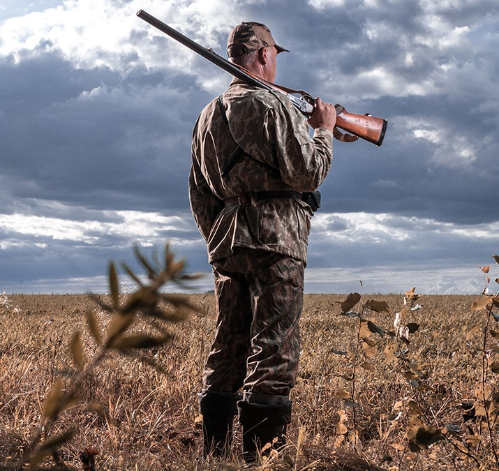 Hunter with a gun on his shoulder against the background of the